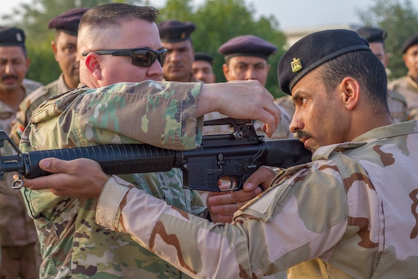 U.S. Army Sgt. 1st Class Michael Garner, left, security forces platoon sergeant assigned to Task Force India Bravo, teaches an Iraqi army primary marksmanship instruction course at Camp Taji, Iraq, Dec.19, 2018.