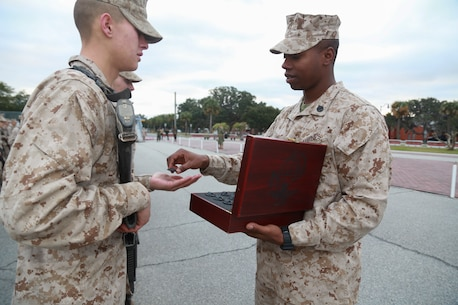 Staff Sgt. John Sharpe, a drill instructor with Platoon 1005, Charlie Company, 1st Recruit Training Battalion, hands a new Marine his Eagle, Globe and Anchor after completing the Crucible hike on Marine Corps Recruit Depot Parris Island, S.C., Dec. 22, 2018. The Crucible is a 54-hour culminating event that requires recruits to work as a team and overcome challenges in order to earn the title United States Marine. (Official Marine Corps photo by Cpl. Sarah Stegall)