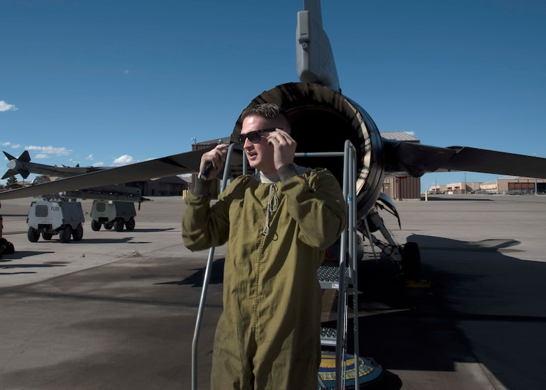 Tech. Sgt. Brandon Brittain, 311th Aircraft Maintenance Unit Dedicated Crew Chief, puts on sunglasses after climbing out of an F-16 Fighting Falcon exhaust Oct. 4 on Holloman Air Force Base, N.M. As a DCC, Brittain is assigned to a specific aircraft, and is responsible for all flight essential maintenance on his aircraft. (U.S. Air Force photo by Airman 1st Class Kindra Stewart)