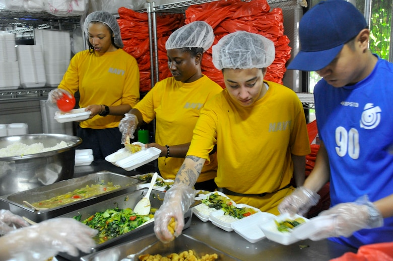 SINGAPORE (Dec. 20, 2018) – Sailors assigned to the submarine tender USS Emory S. Land (AS 39) build meal boxes during a community service event at the Willing Hearts Soup Kitchen in Singapore, Dec. 20. Emory S. Land is a forward-deployed expeditionary submarine tender on an extended deployment conducting coordinated tended moorings and afloat maintenance in the U.S. 5th and 7th Fleet areas of operations.