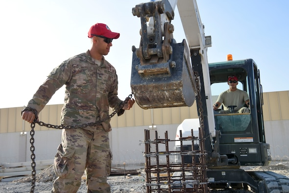 Tech. Sgt. Nathan Michaud, 557th Expeditionary Rapid Engineer Deployable Heavy Operational Repair Squadron, Engineering pavement and equipment operator, ties a chain to an excavator during construction of Air Field Damage repair equipment warehouse, Dec. 23, 2018 at Al Dhafra Air Base, United Arab Emirates.