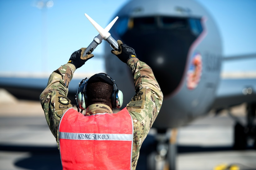 An Airman assigned to the 451st Expeditionary Aircraft Maintenance Squadron signals a KC-135 Stratotanker Aircraft at Kandahar Airfield, Afghanistan Dec. 21, 2018.