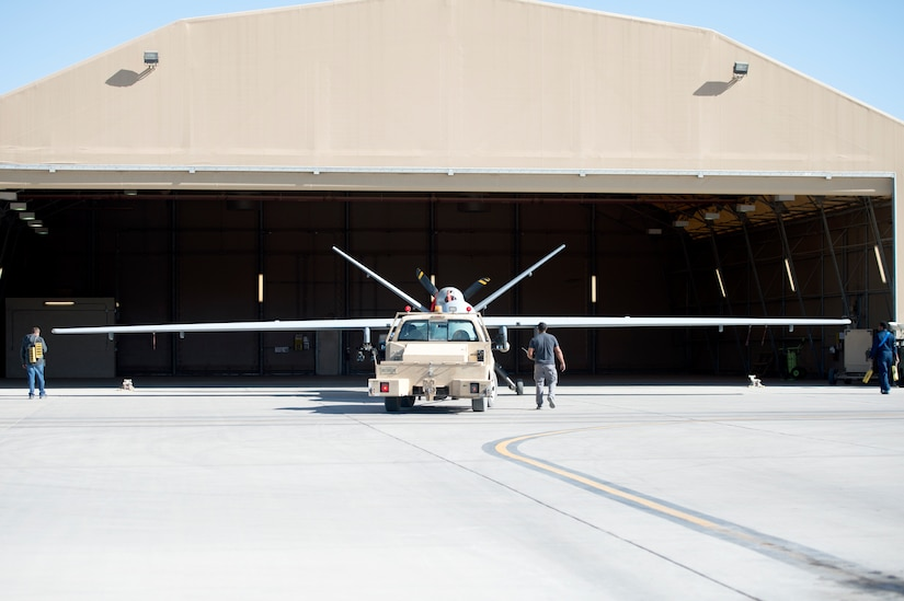 Maintainers assigned to the 451st Expeditionary Aircraft Maintenance Squadron tow an MQ-9 Reaper into a hangar at Kandahar Airfield, Afghanistan Dec 20, 2018.