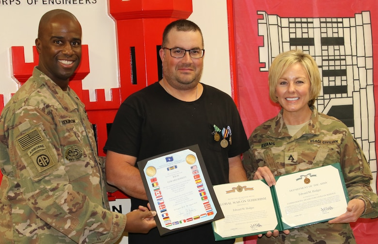 Command Sergeant Major Nate Atkinson and Annette Evans presents Ed Hodges with his End of Tour awards during an impromptu ceremony prior to Hodges' departure.