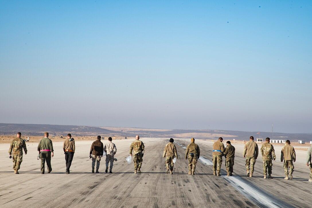 Service members walk along a runway.