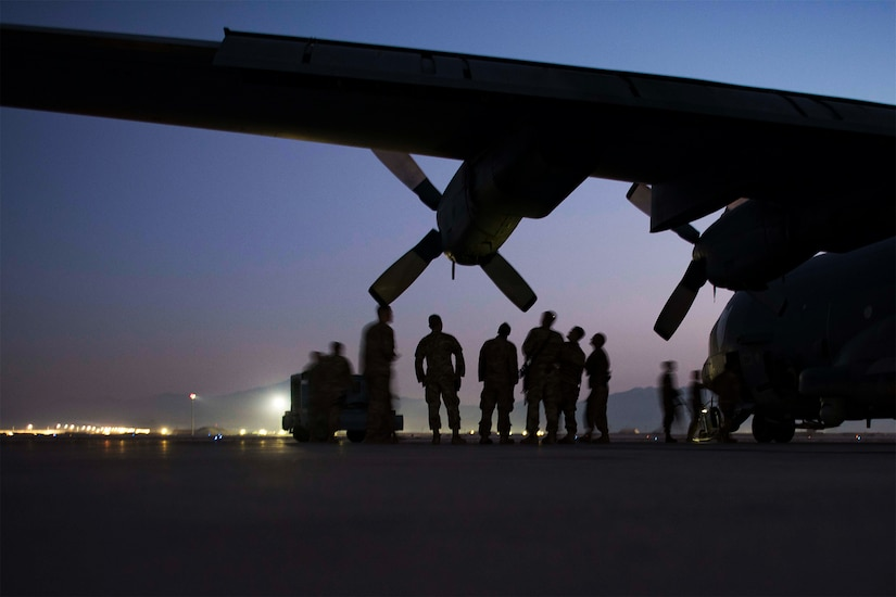 Airmen learn about an aircraft while standing under one of its wings.