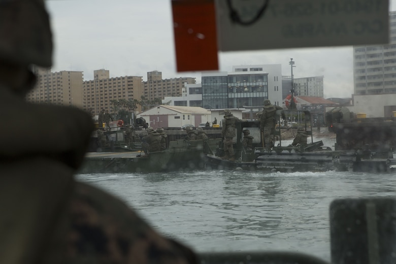 Cpl. Austin Sprague, a combat engineer with Bridge Company, 9th Engineer Support Battalion, Combat Logistics Regiment 35, observes and provides feedback to Marines with Bridge Co. moving an Improved Ribbon Bridge (IRB) bay at Naha Military Port, Okinawa, Japan Jan. 31, 2018. Sprague, a native of Martinsville, Indiana, operated a Bridge Erection Boat for Marines setting up the IRBs. (U.S. Marine Corps photo by Pfc. Jamin M. Powell)