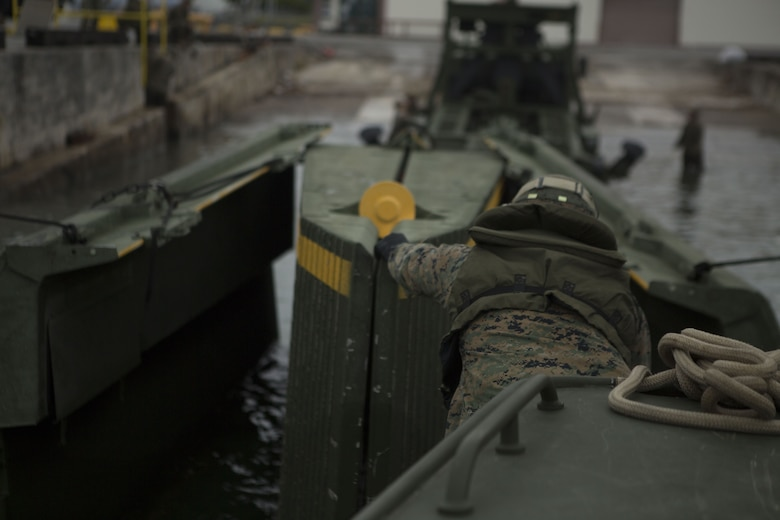 Lance Cpl. Andrew Hollom, a combat engineer with Bridge Company, 9th Engineer Support Battalion, Combat Logistics Regiment 35, reaches for an Improved Ribbon Bridge (IRB) bay to secure it to a Bridge Erection Boat at Naha Military Port, Okinawa, Japan Jan. 31, 2018. Bridge Co. conducted training with IRBs to train new Marines and to show the capabilities of the reactivated company. Hollom is a native of Poplar, Montana. (U.S. Marine Corps photo by Pfc. Jamin M. Powell)