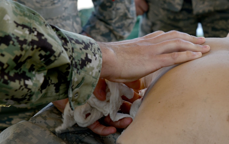A U.S. Navy Petty Officer 2nd Class demonstrates how to pack a wound on a training manikin during Ability to Survive and Operate (ATSO) training at MacDill Air Force Base, Fla., Jan. 26, 2018.