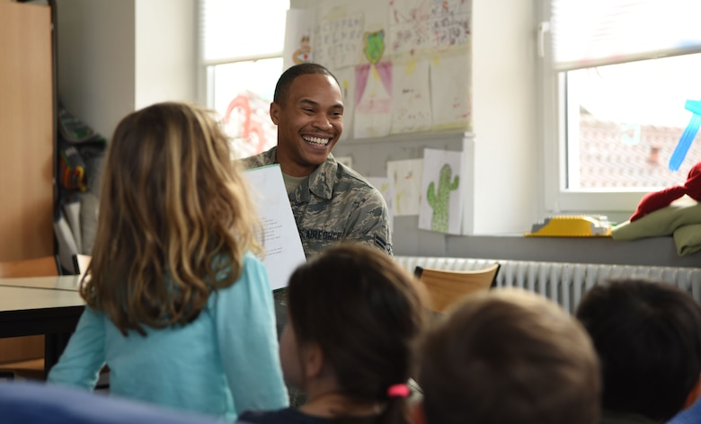 U.S. Air Force Airman 1st Class Milton Hamilton smiles as he reads a children's book to a class of German kindergarteners Jan. 30, 2018 at Villa Winzig in Kaiserslautern, Germany. This was part of an initiative to further support Ramstein Air Base relations with the Kaiserslautern community.