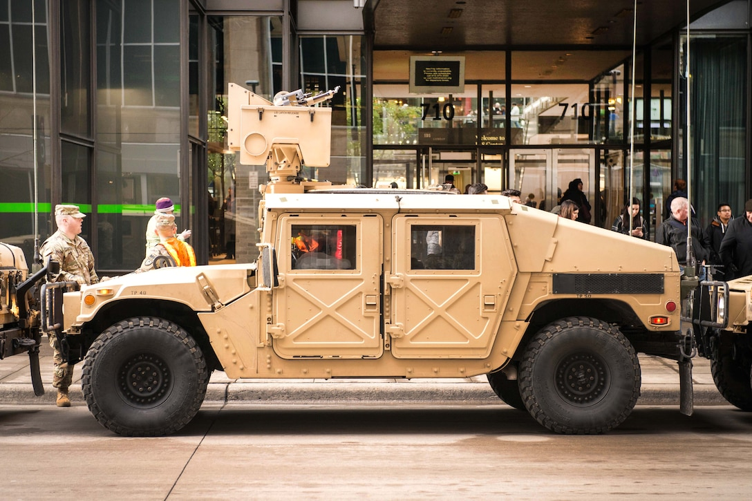A Humvee is parked in front of a building.