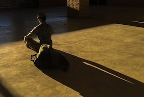 A soldier meditates in an empty room.