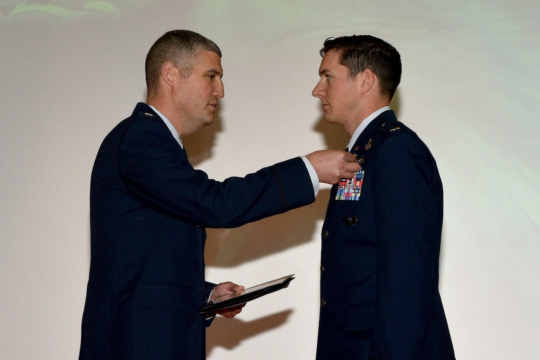 U.S. Air Force Lt. Col. Kenneth Stremmel, 315th Training Squadron commander, presents the Purple Heart medal to 2nd Lt. Daniel Hipps, 315th TRS trainee, during the 315th graduation ceremony in the Base Theater on Goodfellow Air Force Base, Texas, Jan. 31, 2018. The Purple Heart is awarded to members of the U.S. armed forces who were wounded by an instrument of war in the hands of an enemy and posthumously to the next of kin in the name of those who are killed in action or die of wounds received in action. (U.S. Air Force photo by Senior Airman Randall Moose/Released)
