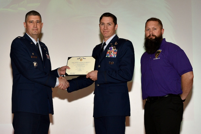 U.S. Air Force Lt. Col. Kenneth Stremmel, 315th Training Squadron commander, presents the Purple Heart certificate to 2nd Lt. Daniel Hipps, 315th TRS trainee, with Military Order of the Purple Heart Chapter 740 Commander, Chris Doggett during, the 315th graduation ceremony in the Base Theater on Goodfellow Air Force Base, Texas, Jan. 31, 2018. Hipps, received the Purple Heart for injuries he received while on deployment in Afghanistan. (U.S. Air Force Photo by Senior Airman Randall Moose/Released)