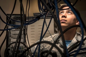 An Airman looks up behind black wires.