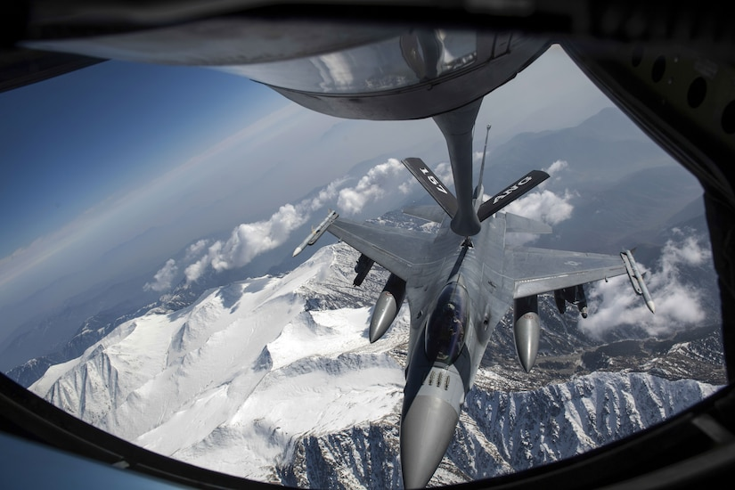 A jet receives fuel from the boom of another aircraft while in flight over snowy mountain peaks.