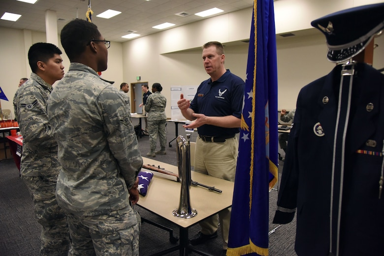 Senior Master Sgt. Larry Davidson, 81st Medical Group infection prevention NCO in charge, right, briefs Airman 1st Class Riverhue Mabanta, left,  and Airman Jordan Edwards, 81st Logistic Readiness Squadron vehicle maintainers, middle, on honor guard duties at the Roberts Consolidated Aircraft Maintenance Facility Jan. 29, 2018, on Keesler Air Force Base, Mississippi. The fair allowed Keesler personnel interested in broadening their career the opportunity to speak with career experts currently serving in a special duty assignment. (U.S. Air Force photo by Kemberly Groue)