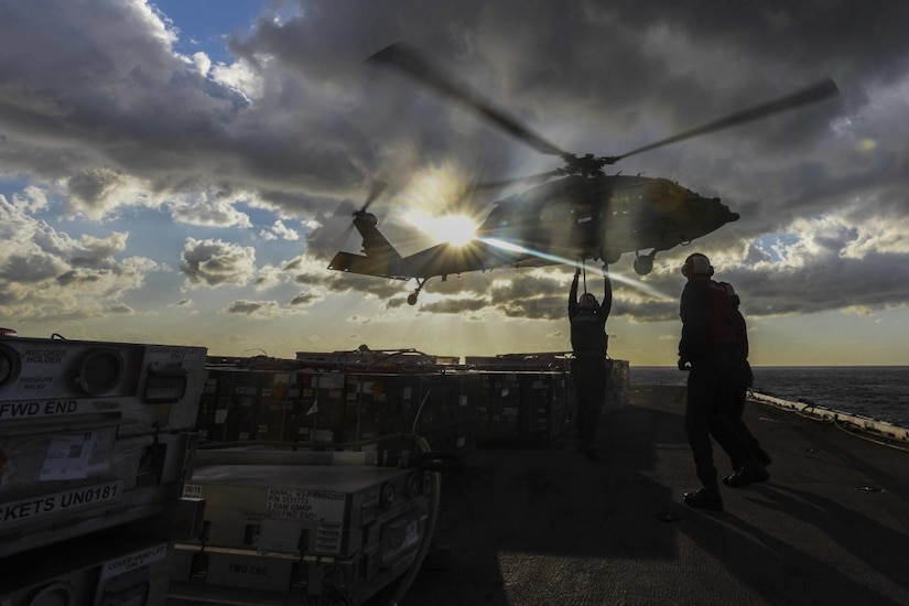 Sailors aboard an aircraft carrier guide a landing helicopter.