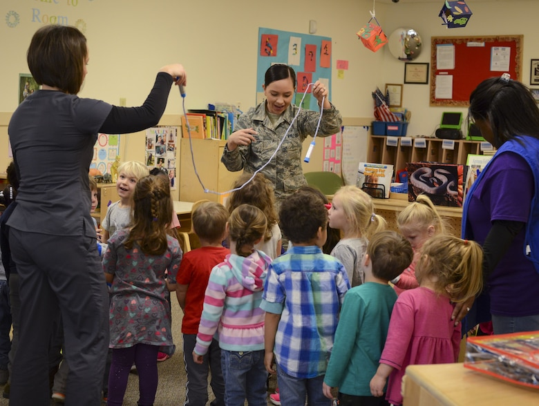 Dental assistants from the 23d Aerospace Medicine Squadron use a jump rope to demonstrate how to floss, Feb. 1, 2018, at Moody Air Force Base, Ga. They visited the Child Development Center as part of National Children's Dental Health Month, to teach children the importance of proper oral care and good habits for taking care of their teeth. (U.S. Air Force photo by Senior Airman Lauren M. Sprunk)