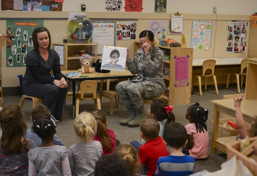 Jessica Puffenbarger, left, and Airman 1st Class Shinique Manders, both 23d Aerospace Medicine Squadron dental assistants, teach children from the child development center about various dental tools, Feb. 1, 2018, at Moody Air Force Base, Ga. Airmen from the 23d AMDS visited the Child Development Center as part of National Children's Dental Health Month, to teach children the importance of proper oral care and good habits for taking care of their teeth. (U.S. Air Force photo by Senior Airman Lauren M. Sprunk)