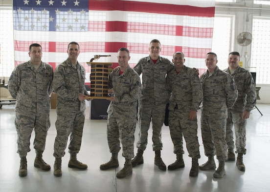 366th Maintenance Group commander Col. Scott Grover presents the trophy for the quarterly load competition to the 389th Aircraft Maintenance Unit January 29, 2018, at Mountain Home Air Force Base, Idaho. The maintenance load competition simulates the pressure of a deployed environment when load crews work quickly and efficiently to prepare jets for missions. (U.S. Air Force photo by Senior Airman Chester Mientkiewicz)