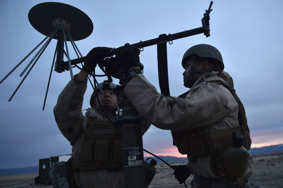 Senior Airmen Yuhao Huang and Zyrus Medina, 821st Contingency Response Support Squadron frequency technicians, set-up a line of sight antenna while deployed to Amedee Army Airfield, Calif., as part of a week-long readiness exercise, Jan. 31, 2018.  The exercise evaluated the Airmen's readiness and ability to execute and sustain rapid global mobility around the world. (U.S. Air Force photo by Tech. Sgt. Liliana Moreno/Released)