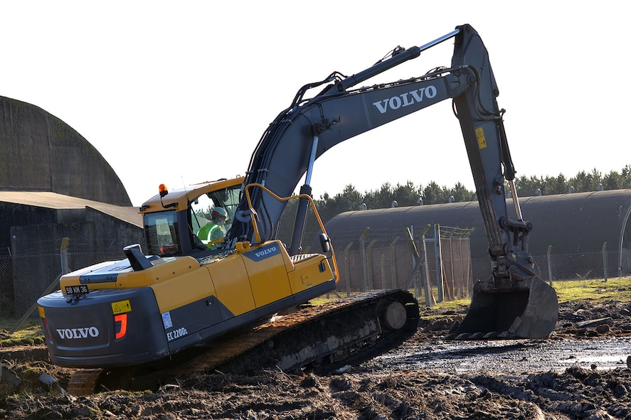 """U.S. Air Force Staff Sgt. William Baynard, 100th Civil Engineer Squadron pavements and equipment supervisor, drives an excavator used by the British Army at Rock Barracks, Woodbridge, England, Jan. 25, 2018. The excavator followed the jack hammer – used to initially break up the concrete – and rip up chunks of it to be hauled away. Using the equipment gave the 100th CES Airmen valuable """"stick time,"""" which they are not easily able to get as there are no excavators at RAF Mildenhall. (U.S. Air Force photo by Karen Abeyasekere)"""