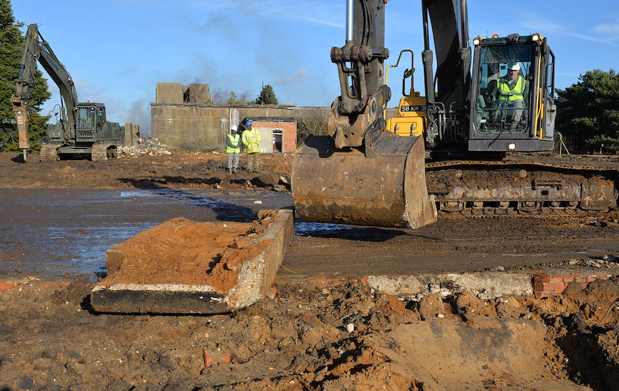 "U.S. Air Force Staff Sgt. William Baynard, 100th Civil Engineer Squadron pavements and equipment supervisor, breaks up a concrete apron using a British Army excavator at Rock Barracks, Woodbridge, England, Jan. 25, 2018. The excavator followed the jack hammer – used to initially break up the concrete – and ripped up chunks of it to be hauled away. Using the equipment gave the 100th CES Airmen valuable ""stick time,"" which they are not easily able to get as there are no excavators at RAF Mildenhall. (U.S. Air Force photo by Karen Abeyasekere)"