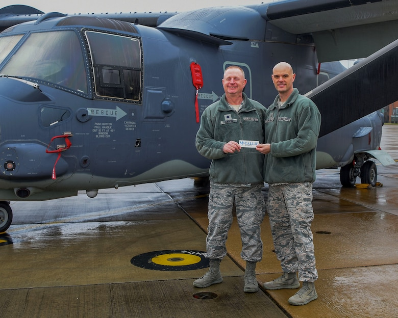 Chaplain (Lt. Col.) Ronald Ragon and Chaplain (Capt.) Joseph Wright, 100th Air Refueling Wing chaplains, stand in front of CV-22 holding a McCallie School bumper sticker on Dec. 21, 2017 on RAF Mildenhall, England. (U.S. Army photo by Staff Sgt. Philip Steiner )