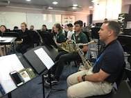 U.S. Air Force Staff Sgt. Lencys Esteban Nunez, a saxophonist with the AFCENT band, reviews music with local students at a school within the United Arab Emirates, Jan. 28, 2018.The band members assisted music instructors during classes lending advice and encouragement to students while on campus. Following the academic portion, the band held a performance during lunch by playing popular music. (U.S. Air Force photo by Tech Sgt. Anthony Nelson Jr.)