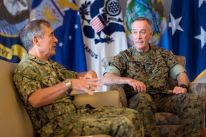 Two military leaders sit on a couch and chair talking.