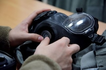 A U.S. Airman assigned to the 100th Air Refueling Wing inspects the filter of his M50 gas mask during a chemical, biological, radiological and nuclear defense survival skills class at RAF Mildenhall, England, Jan. 23, 2018. The M50 gas mask is a key part of protection against air-borne contaminants. (U.S. Air Force photo by Senior Airman Alexandra West)