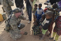 U.S. Air Force Tech Sgt. Douglas N. Spangler, 822nd Expeditionary Base Defense Squadron Security Forces squad leader, speaks to children from a nearby village outside of Air Base 201, Niger, Dec. 11, 2017. Spangler led a 13-member patrol team to find a missing two-year-old girl who was lost for six hours outside of Air Base 201. (U.S. Air Force photo by Staff Sgt. Joshua Dewberry)