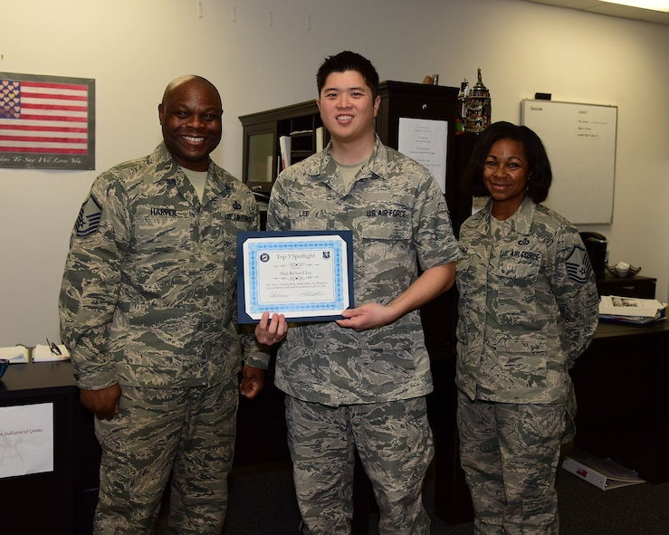 Staff Sgt. Richard Lee, 14th Operations Support Squadron Quality Assurance Non-Commissioned Officer in charge for Aircrew Flight Equipment, receives the Columbus Air Force Base Top 3 Spotlight from Master Sgt. Demetri Harper, Top Three Vice President and Master Sgt. Carmina Beedle, 14th OSS AFE Superintendent, Jan. 24, 2018, on Columbus Air Force Base, Mississippi. He is also the lead Aircrew Continuation Training instructor for roughly 684 instructor, student, and international pilots. Staff Sgt. Lee was hand-selected by the current operations flight commander to conduct training for the Vice Chief of Staff Headquarters of the United States Air Force, for his T-6 flight. (U.S. Air Force photo by Elizabeth Owens)