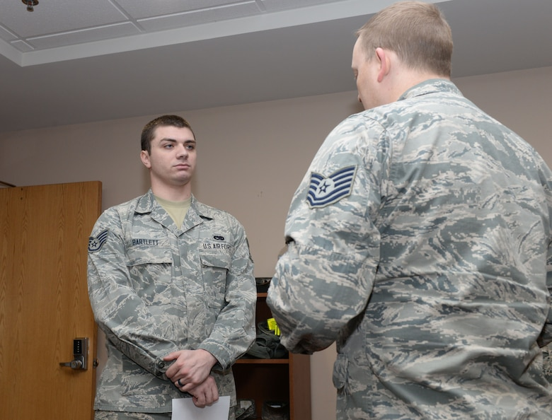 Staff Sgt. Devin Bartlett, a B-1 Bomber crew chief assigned to the 28th Aircraft Maintenance Squadron, receives his 7-level career development course results from Tech. Sgt. Jed Abbott, the base education and training manager assigned to the 28th Force Support Squadron, inside the Rushmore Center at Ellsworth Air Force Base, S.D., Jan. 18, 2018. Air Force specialty codes are broken into five levels of proficiency, with the 1-level being a helper and a 9-level being a superintendent-type proficiency. (U.S Air Force photo by Airman 1st Class Nicolas Z. Erwin)