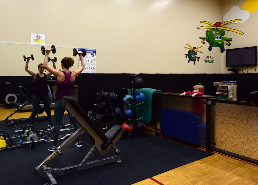A member of Team Whiteman uses the parent/child activity room in the Fitness Center at Whiteman Air Force Base, Mo., Jan. 24, 2018. Exercise equipment such as treadmills and assorted weights are available to use while children play in an enclosed area with toys and playsets. (U.S. Air Force photo by Staff Sgt. Danielle Quilla)