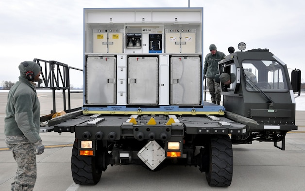 Senior Airman Michael Thompson, left, part of the air transportation crew securing an air transportable galley-lavatory on a 25K Halvorsen Loader bound for Hickam Hickam Air Force Base, Hawaii, in support of exercise Sentry Aloha