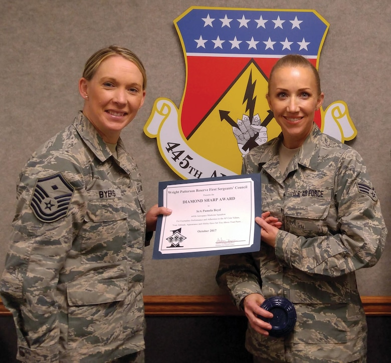 Master Sgt. Ashley Byers, 14th Intelligence Squadron first sergeant, presents the October 2017 Diamond Sharp Award to Senior Airman Pamela Boyd, 445th Aerospace Medicine Squadron, during the January 6, 2018 unit training assembly.