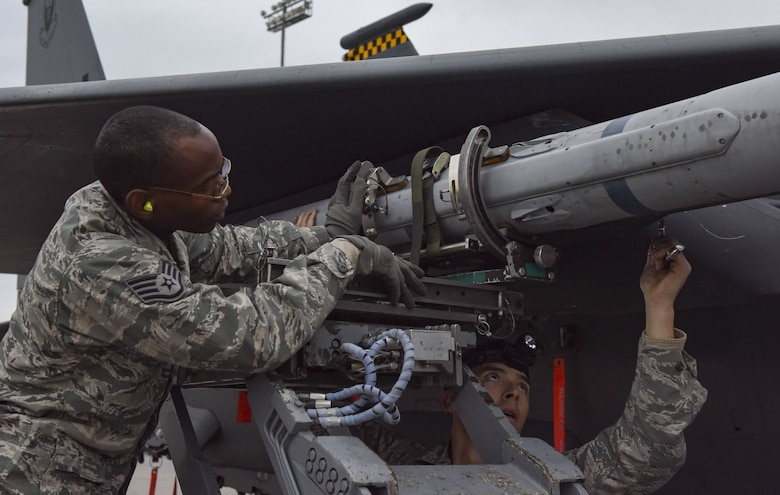 Staff Sgt. Mekai Stewart and Staff Sgt. Brett Rosales-Carr, both 57th Aircraft Maintenance Squadron load crew members, load an AIM-120 missile onto an F-15 Eagle during the load crew competition of the year at Nellis Air Force Base, Nev., Jan. 8, 2018. Load crew competitions challenge the teams' capabilities to load munitions on aircraft in an accurate, safe and timely manner. (U.S. Air Force photo by Airman 1st Class Andrew D. Sarver)