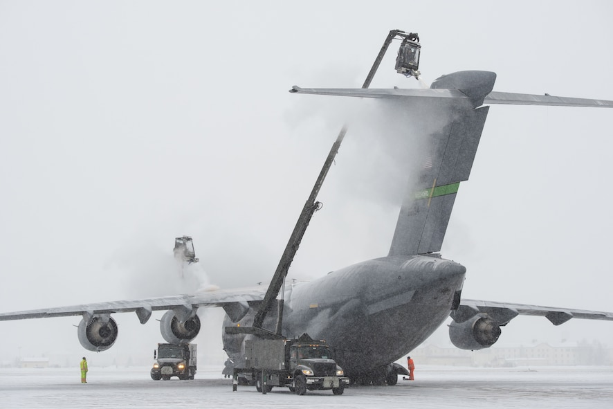 Airmen assigned to the 732nd Air Mobility Squadron de-ice a C-17 Globemaster III out of Joint Base Lewis-McChord, Wa., while conducting flight operations at Joint Base Elmendorf-Richardson, Alaska, Jan. 25, 2018. During the harsh Alaskan winters de-icing keeps aircraft operational by removing layers of snow, ice and frost that could adversely affect flights. (U.S. Air Force photo by Alejandro Peña)