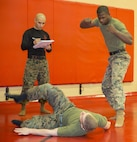 Cpl. Cody Marx, legal services non-commissioned officer, U.S. Marine Corps Forces Command, demonstrates a proper break-fall technique after a shoulder throw from Sgt. Lloyd Williams, assistant landing force operational reserve material