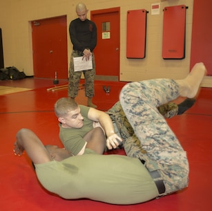 "Cpl. Cody Marx, legal services non-commissioned officer, U.S. Marine Corps Forces Command, demonstrates the ""arm-bar from guard"" technique on Sgt. Lloyd Williams, assistant landing force operational reserve material warehouse chief, G4, MARFORCOM, while Staff Sgt. Frankie Ruiz, warehouse chief, G4, MARFORCOM observes during a Marine Corps Martial Arts Program belt exam at Hopkins Hall gym aboard Camp Allen, Va., Jan. 31. Marx was being tested on several strikes, arm and wrist manipulations, and throws in order to earn his  green belt in MCMAP. (Official U.S. Marine Corps photo by Chris Jones/Released)"