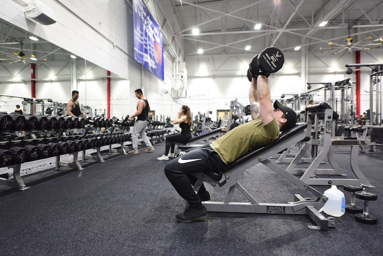 U.S. Air Force Senior Airman Nicholas Mastroiani, an installation controller assigned to the 509th Security Forces Squadron, performs dumbbell bench presses in the Fitness Center weight room at Whiteman Air Force Base, Mo., Jan. 24, 2018. The Fitness Center features specialty weight equipment and a large assortment of free weights for those with strength training and muscle toning in mind. (U.S. Air Force photo by Staff Sgt. Danielle Quilla)