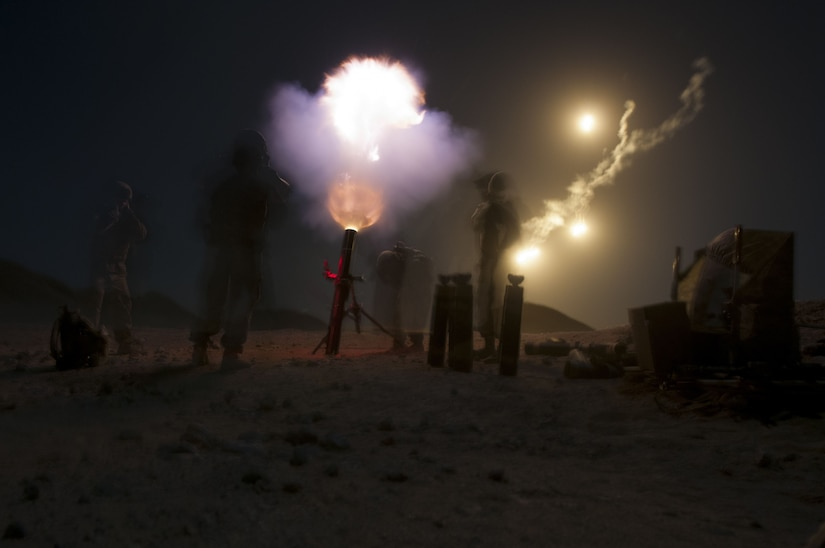 A mortar crew fires illumination rounds into the night.