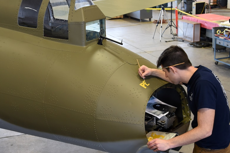(02/01/2018) Museum restoration specialist Casey Simmons paints the names Pete and Repeat on the tail gun position of the Boeing B-17F Memphis Belle during the restoration process. SSgt. John Quinlan, the tail gunner of the Memphis Belle crew, named the guns Pete and Repeat during WWII. Quinlan also received credit for shooting down one German fighter which is represented by the swastika. (U.S. Air Force photo by Ken LaRock)