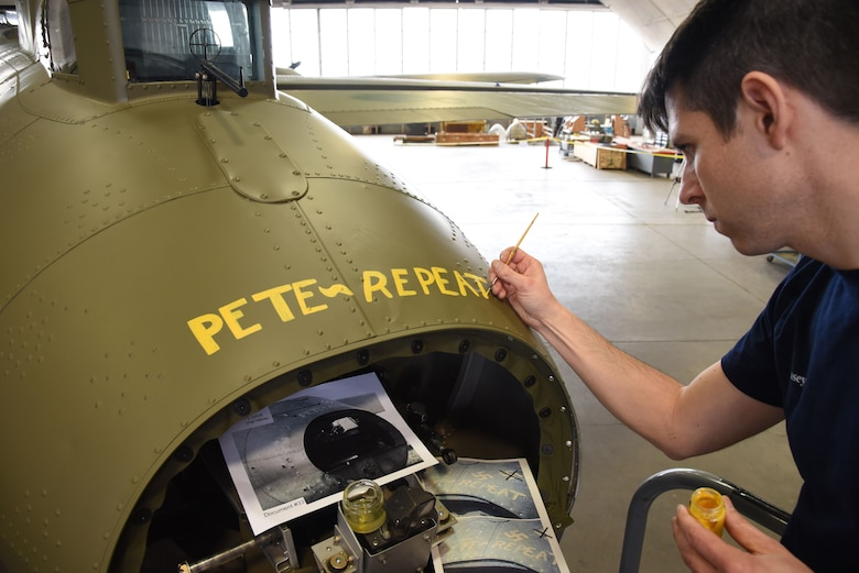 (02/01/2018) Museum restoration specialist Casey Simmons paints the names Pete and Repeat on the tail gun position of the Boeing B-17F Memphis Belle during the restoration process. SSgt. John Quinlan, the tail gunner of the Memphis Belle crew, named the guns Pete and Repeat during WWII. (U.S. Air Force photo by Ken LaRock)