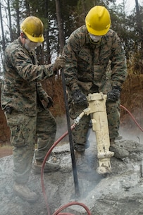 Marine Corps Pfc. Nathaniel Ford, right, a combat engineer with 8th Engineer Support Battalion, 2nd Marine Logistics Group, demolishes concrete with a jackhammer aboard Camp Lejeune, N.C., Jan. 29, 2018. The land was cleared to make room to facilitate more advanced future structures being constructed. (U.S. Marine Corps photo by Lance Cpl. Tyler W. Stewart)