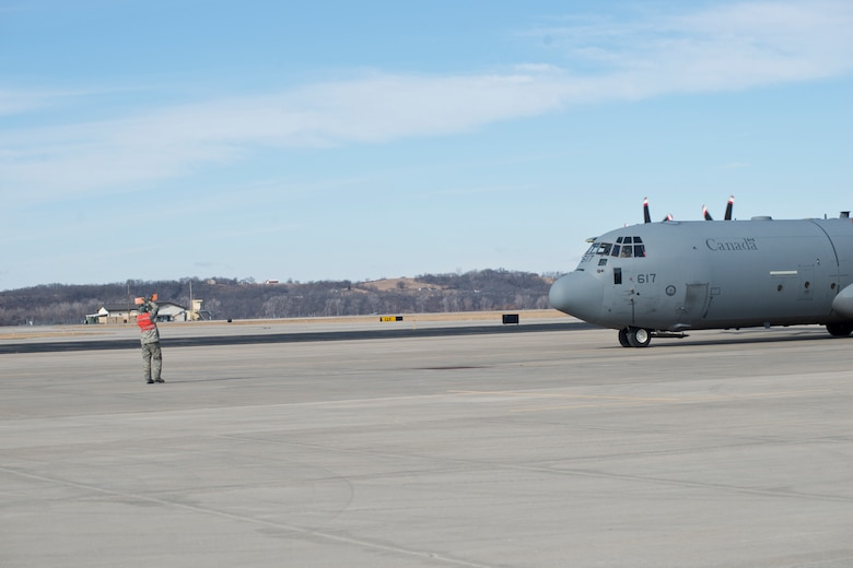 A 139th Airlift Wing member marshals a Royal Canadian Air Force CC-130J aircraft at Rosecrans Memorial Airport, St. Joesph, Mo. February 1, 2018 after a training flight for the Treaty on Open Skies. Personnel from the United States, Canada, United Kingdom, France and the Czech Republic participated in the flight designed to promote international cooperation and transparency. (U.S. Air National Guard photo/Tech. Sgt. John Hillier)