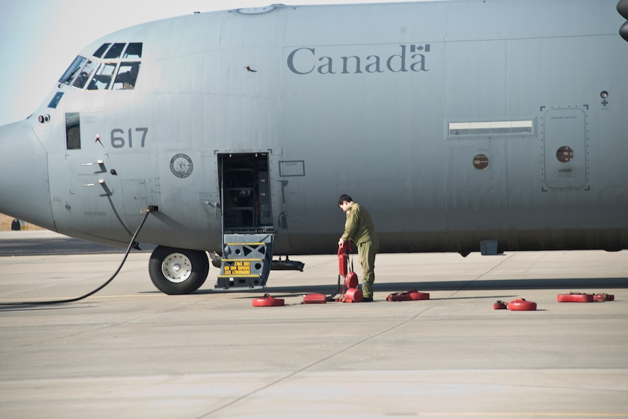 A Royal Canadian Air Force member chocks the wheels of his CC-130J aircraft at Rosecrans Memorial Airport, St. Joesph, Mo. February 1, 2018 after a training flight for the Treaty on Open Skies. Personnel from the United States, Canada, United Kingdom, France and the Czech Republic participated in the flight designed to promote international cooperation and transparency. (U.S. Air National Guard photo/Tech. Sgt. John Hillier)