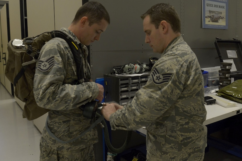 U.S. Air Force Staff Sgt. Brian Spears, right, 437th OSS aircrew flight equipment lead trainer, shows U.S. Air Force Staff Sgt. Justin Stepleton, left, 437th Operations Support Squadron NCO in charge of the AFE flotation section, proper procedures for donning equipment Feb. 1, 2018.